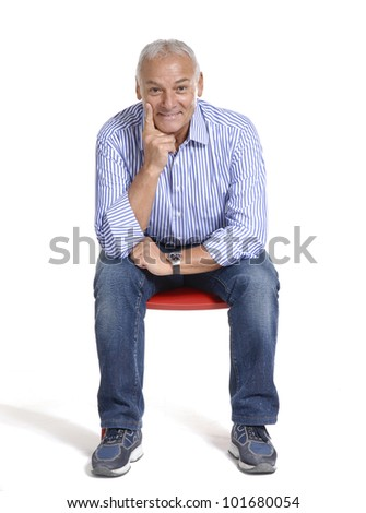 Portrait of a casual senior sitting on a chair on white background. - stock photo