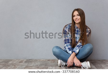 Portrait of a casual woman sitting on the floor and looking away on gray background - stock photo