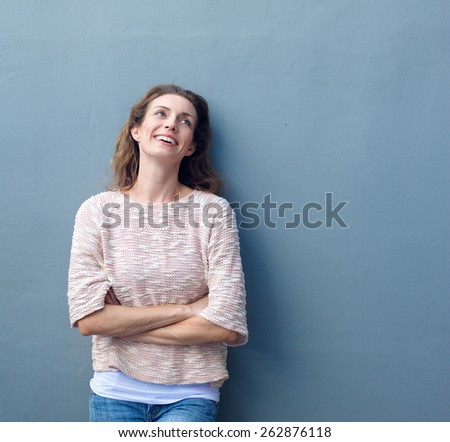 Portrait of a casual woman smiling with arms crossed on gray background - stock photo