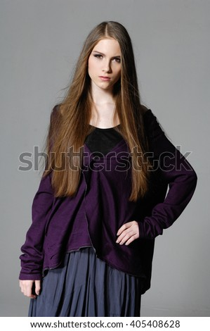 portrait of a casual young fashion model posing-gray background  - stock photo