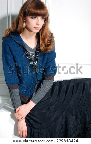 portrait of a casual young fashion model sitting - stock photo