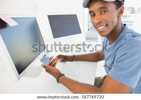 Portrait of a casual young man doing online shopping through computer and credit card in office