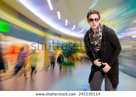 Portrait of a casual young man in sunglasses in the mall - stock photo