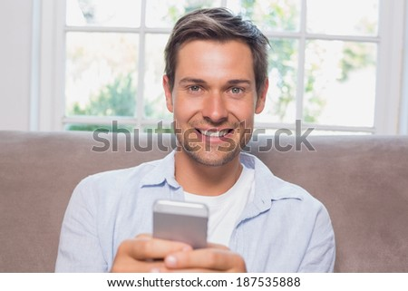 Portrait of a casual young man reading text message on sofa at home - stock photo