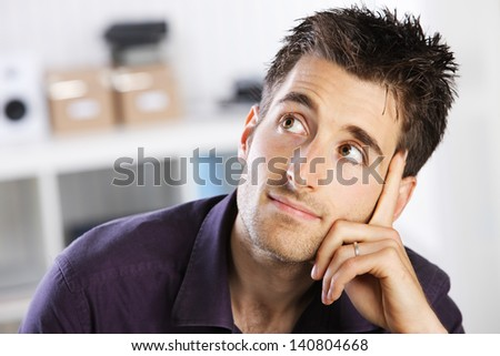 Portrait of a casual young man thinking - stock photo