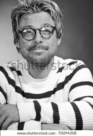 Portrait of a casual young man with glasses. Short blond hair. Black and white. Studio portrait.