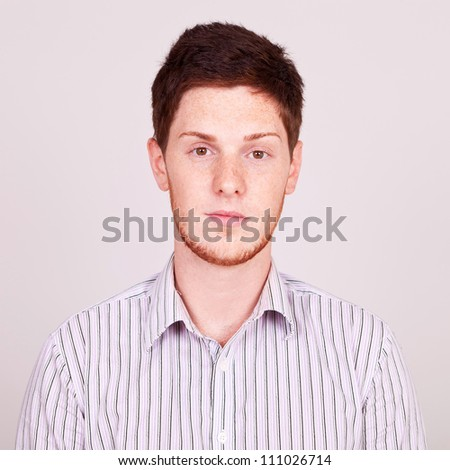 portrait of a casual young red-haired, freckled and bearded man on gray background - stock photo
