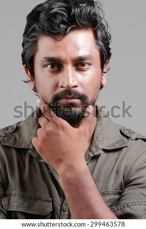Portrait of a casually dressed Indian young man with beard.Harsh light and shadow treatment. - stock photo
