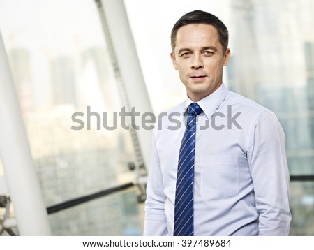 portrait of a caucasian business executive standing by the window in office. - stock photo