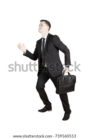 Portrait of a Caucasian businessman carrying a briefcase while posing to step upward, isolated on white background
