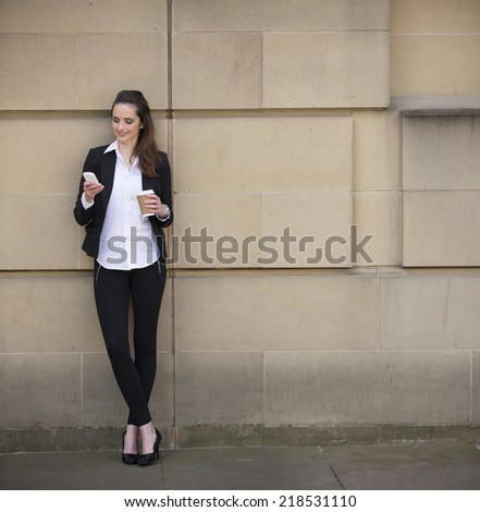 Portrait of a Caucasian businesswoman standing outside using mobile phone to send a message. - stock photo