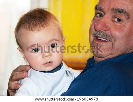 Portrait of a caucasian happy grandfather and grandson. Smiling 60 year positive senior elderly man with baby. Close up, indoor. - stock photo