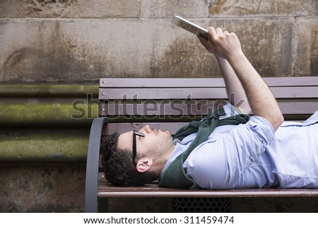 Portrait of a Caucasian man having a break on a city bench & reading Tablet PC. Young urban man in City.
