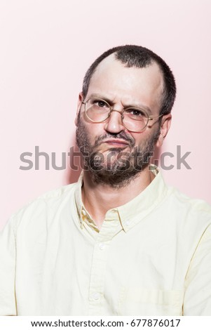 Portrait of a caucasian man in his thirties, wearing a pale yellow shirt against pastel pink background.