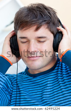 Portrait of a caucasian man listening to music with closed eyes sitting in his living-room