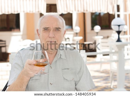 Portrait of a Caucasian senior man holding a glass of brandy at a restaurant - stock photo