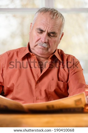 Portrait of a Caucasian senior man wearing mustache and a brick-red shirt while sitting at the table reading the daily newspaper with a serios and worried facial expression