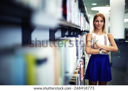 Portrait of a caucasian smiling female student holding book while standing in university library, pretty young woman standing near bookshelves in bookstore shop, exam preparation in university