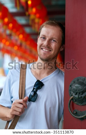 Portrait of a caucasian tourist leaning against a red traditional oriental door with chinese lanterns in background of modern asian city - stock photo