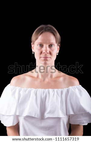 Portrait of a Caucasian Woman with White Dress with Open Shoulders Isolated on a Black Background.
