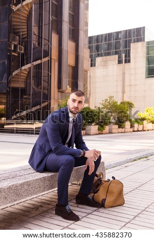 Portrait of a caucasian young businessman seated on a bench outside the office, resting in a coffee break time - stock photo
