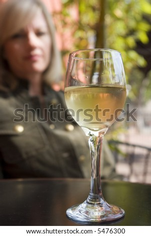 Portrait of a champagne glass with a woman in the background