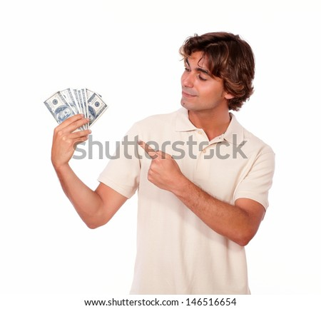 Portrait of a charismatic young adult holding cash money and pointing it while standing on white background