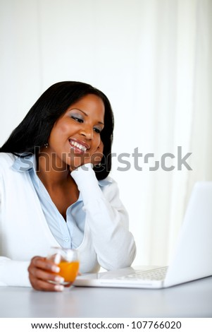 Portrait of a charming and relaxed woman smiling and reading on laptop screen at soft composition - stock photo