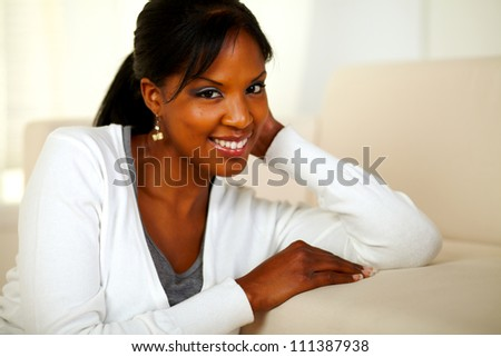 Portrait of a charming black woman looking and smiling at you. With Copyspace