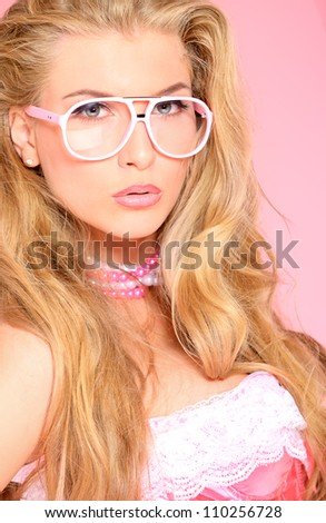 Portrait of a charming blonde woman in pink spectacles posing in studio over pink background.