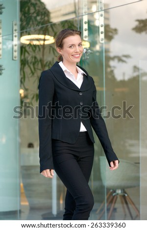 Portrait of a charming business woman walking outside in the city - stock photo