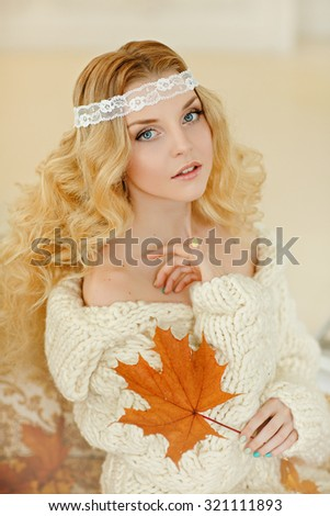 Portrait of a charming, delicate and very cute girl blonde in a white knit sweater with a maple leaf in the hands, in the bright house