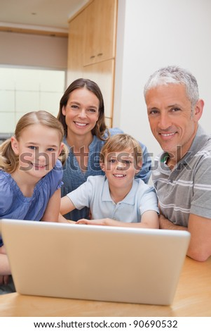 Portrait of a charming family using a laptop in their kitchen - stock photo