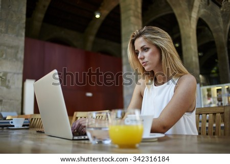 Portrait of a charming female student keyboarding something on net-book while relaxing after lectures in University, beautiful freelancer woman working on laptop computer during coffee break in cafe  - stock photo