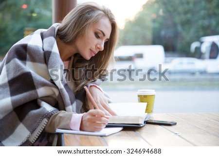 Portrait of a charming girl doing homework in cafe - stock photo
