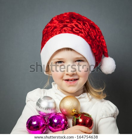 Portrait of a charming little girl in Santa's hat, grey background
