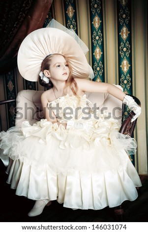 Portrait of a charming little lady in a beautiful elegant dress posing in a vintage interior.  - stock photo
