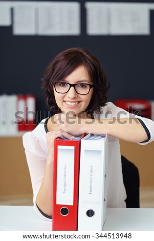 Portrait of a Charming Office Woman Leaning on File Binders on Top of the Table and Looking at the Camera with Happy Facial Expression. - stock photo