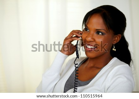 Portrait of a charming relaxed woman speaking on phone at home indoor