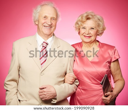 Portrait of a charming retired couple posing against pink background - stock photo
