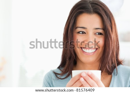 Portrait of a charming woman enjoying a cup of coffee in the kitchen - stock photo