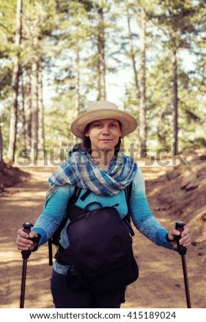 Portrait of a charming woman hiker in a straw hat standing on a forest trail. Sunny day on Cyprus. Toned image. - stock photo