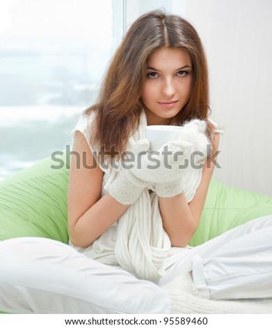 Portrait of a charming woman holding a cup of tea and daydreaming - stock photo