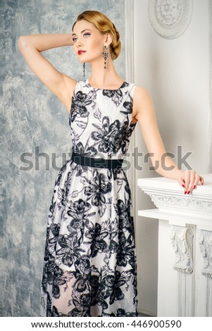 Portrait of a charming woman in beautiful evening dress standing by a fireplace in a room with classical vintage interior. Jewellery. Fashion shot. Hairstyle. Make-up, cosmetics. - stock photo