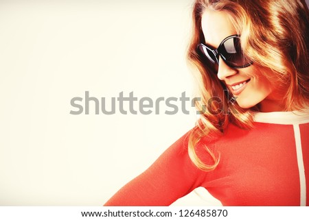 Portrait of a charming woman in red dress and sunglasses. - stock photo