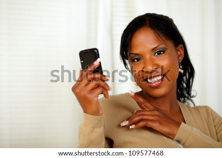 Portrait of a charming woman reading a message on cellphone while looking at you - stock photo