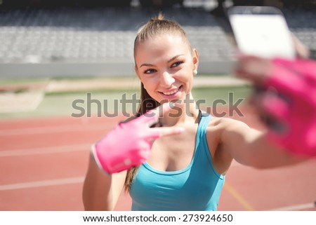 Portrait of a charming woman taking a selfie, a picture of herself during training. Training, fitness and technology outdoors - stock photo
