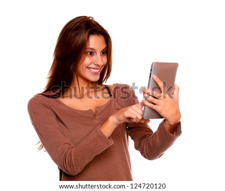 Portrait of a charming young female with long brown hair reading on tablet pc screen against white background