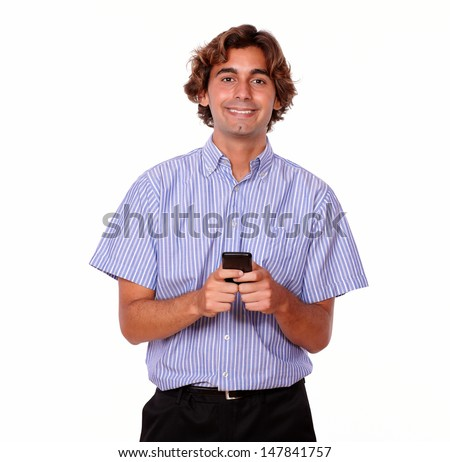 Portrait of a charming young man calling on mobile while is standing in blue shirt on isolated background