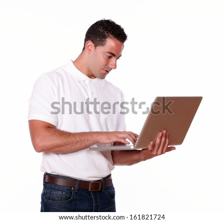 Portrait of a charming young man on white t-shirt and jeans working on his laptop computer while standing on isolated studio